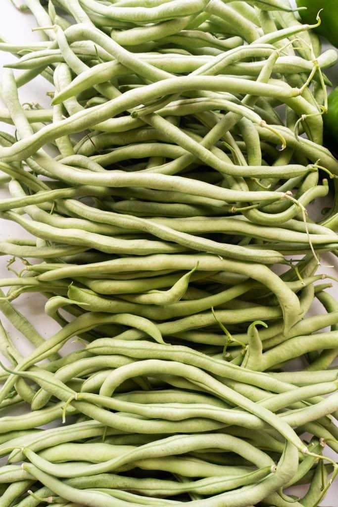 lots of green bean on white table