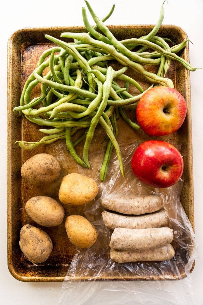 fresh green beans, potatoes, apples and sausage on baking sheet showing the list of ingredients