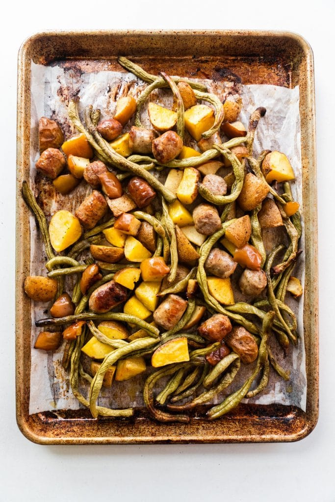 sausage, green beans, potatoes and apples on a baking sheet with parchment paper