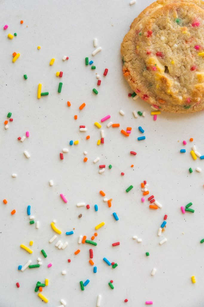 half of funfetti cookie on white table with rainbow sprinkles