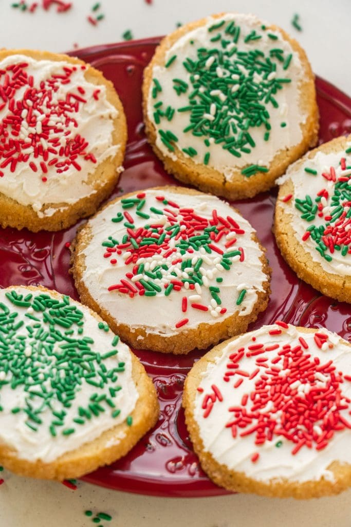 christmas cookies with sprinkles sitting on red plate