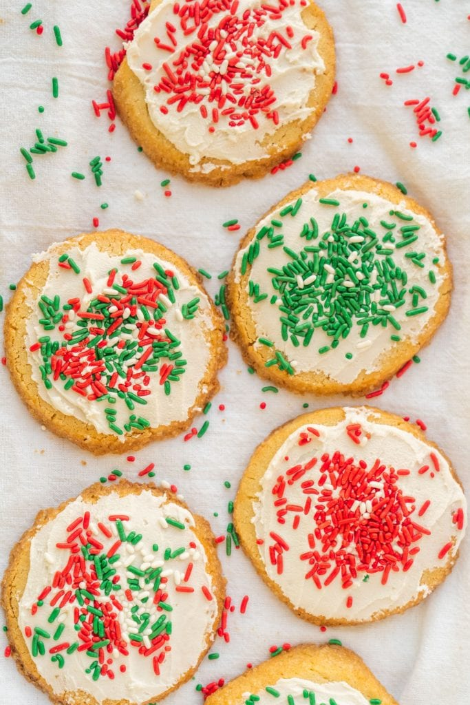 christmas shortbread cookies with white frosting and red and green sprinkles sitting on white towel