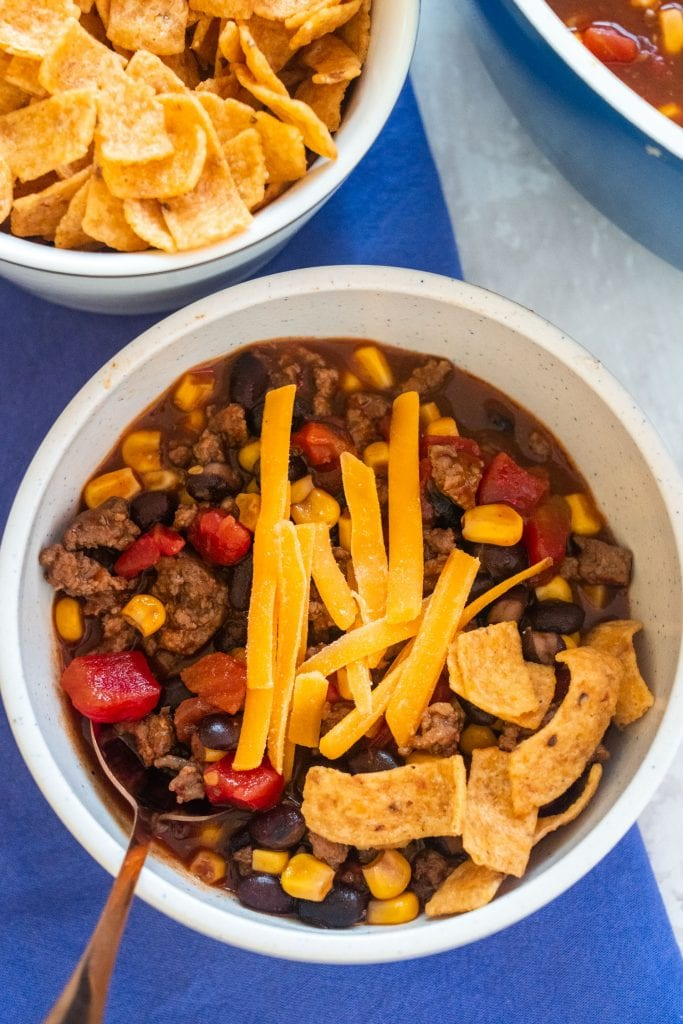 white bowl filled with black bean stew with bowl of fritos nearby on table