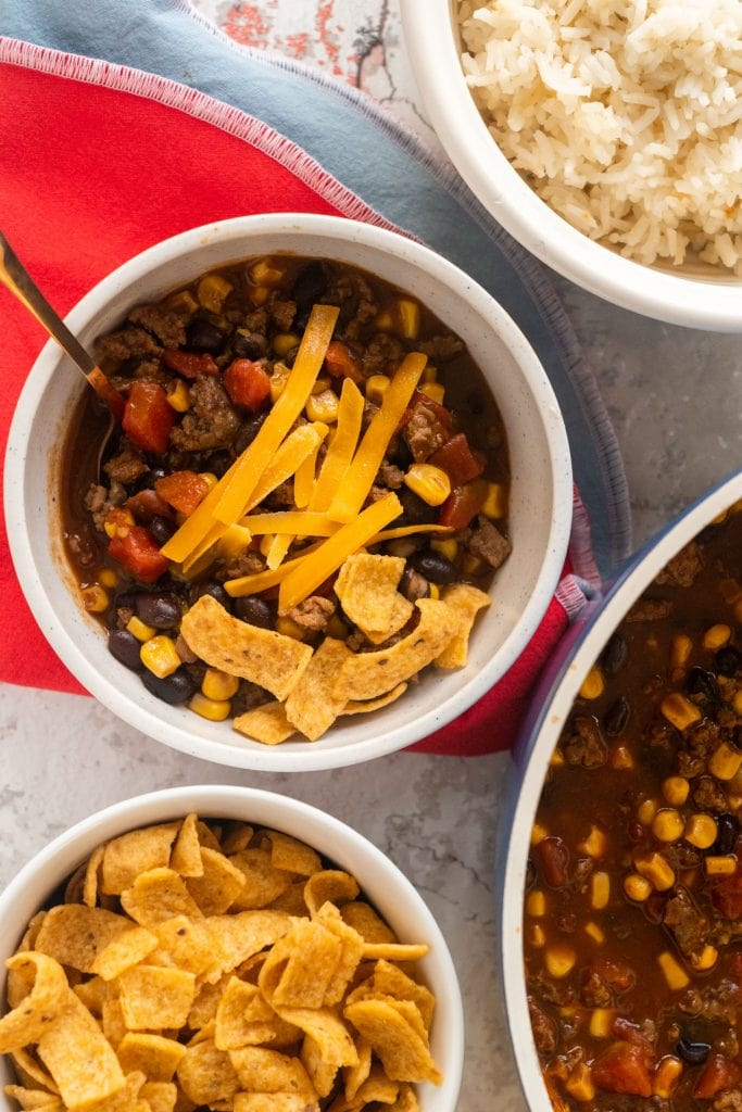 bowl of black bean stew next to bowl of white rice, bowl of fritos and large bowl of soup