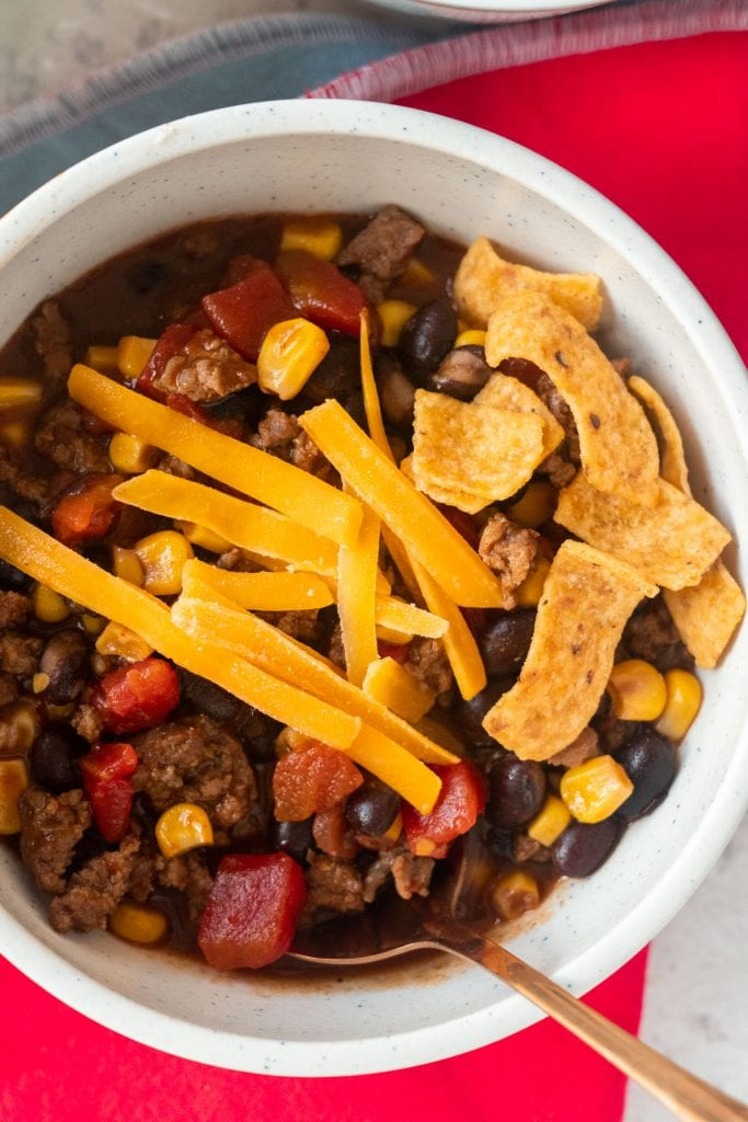 black bean soup in white bowl with bronze spoon, cheese and fritos on top