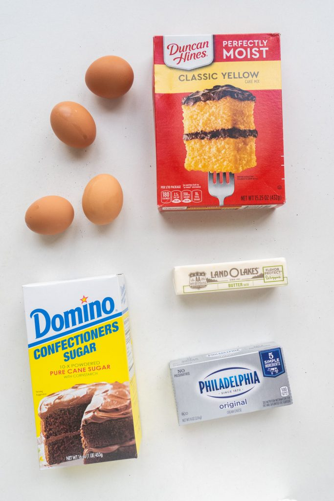 ingredients on table, cake mix, eggs, butter, sugar and cream cheese