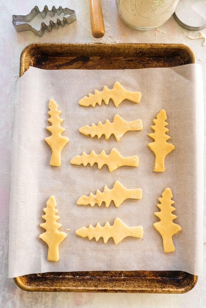 christmas tree sugar cookies cut out on parchment paper lined cookie sheet