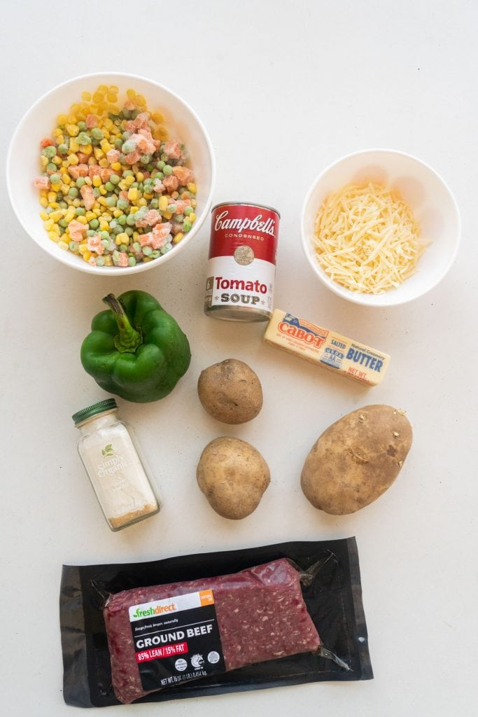 ingredients on white table, frozen vegetables, tomato soup, shredded cheese, butter, pepper, potatoes, onion powder and ground beef
