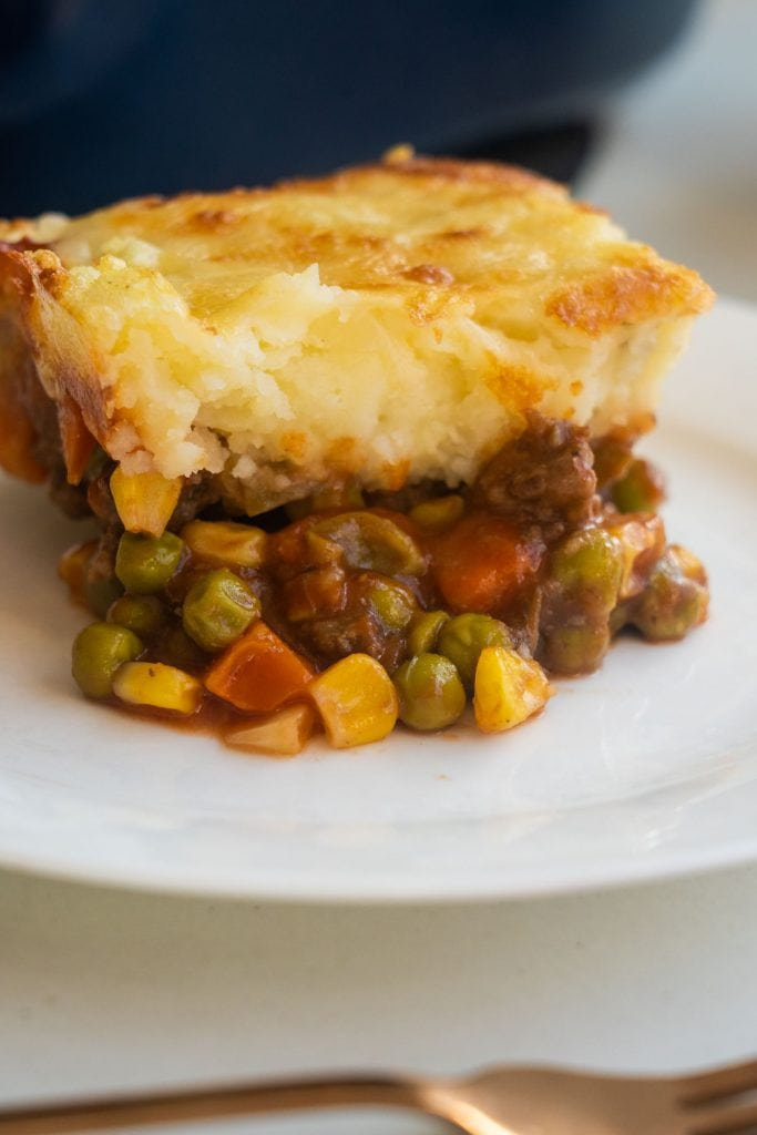 easy to make shepherd's pie with buttery mashed potatoes on top on white plate