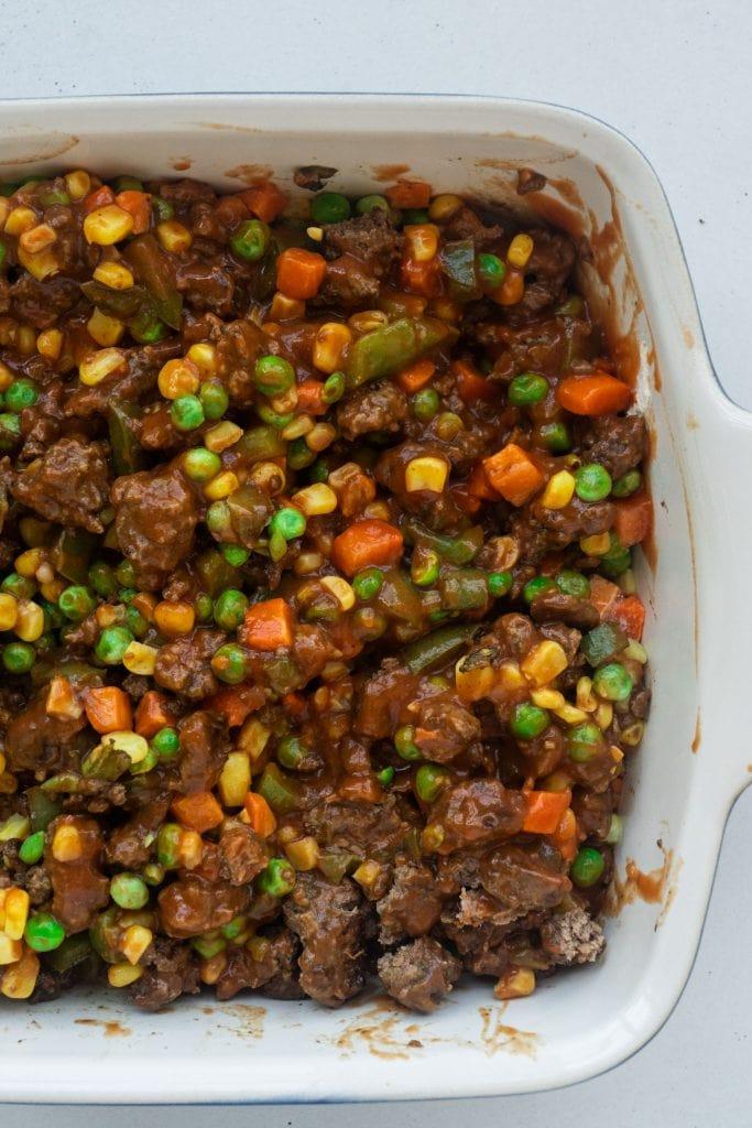 ground beef mixture with frozen vegetables spread in 8x8 baking dish