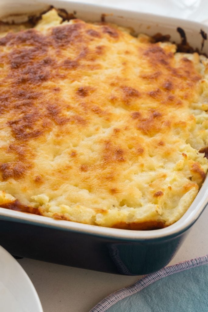 baked shepherd's pie with golden brown cheese on mashed potatoes in casserole dish
