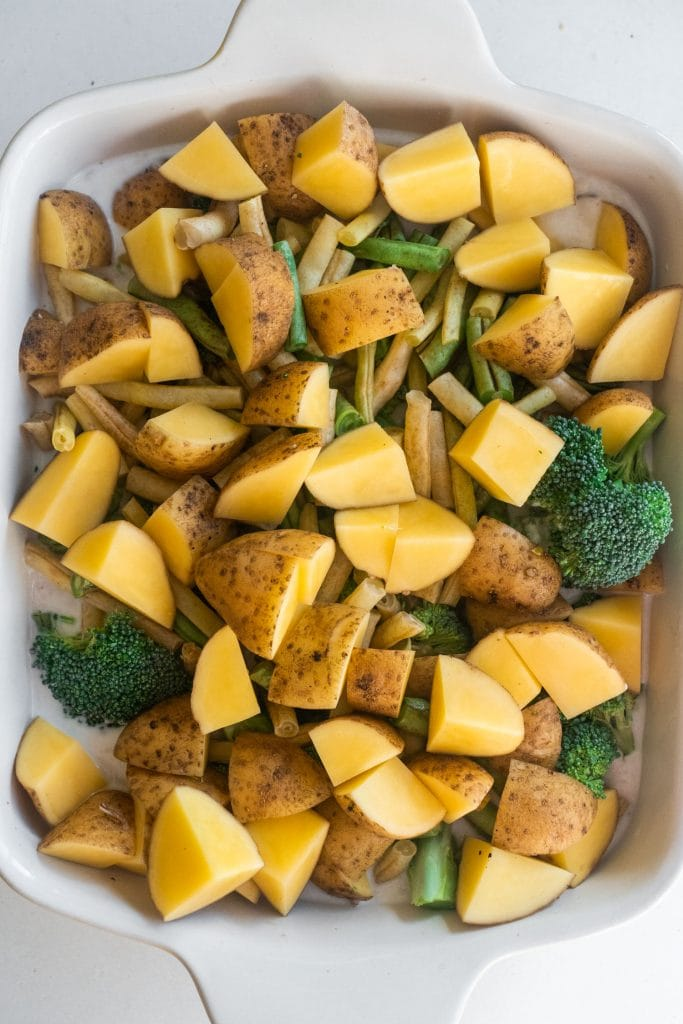 potatoes, green beans and broccoli in white baking dish