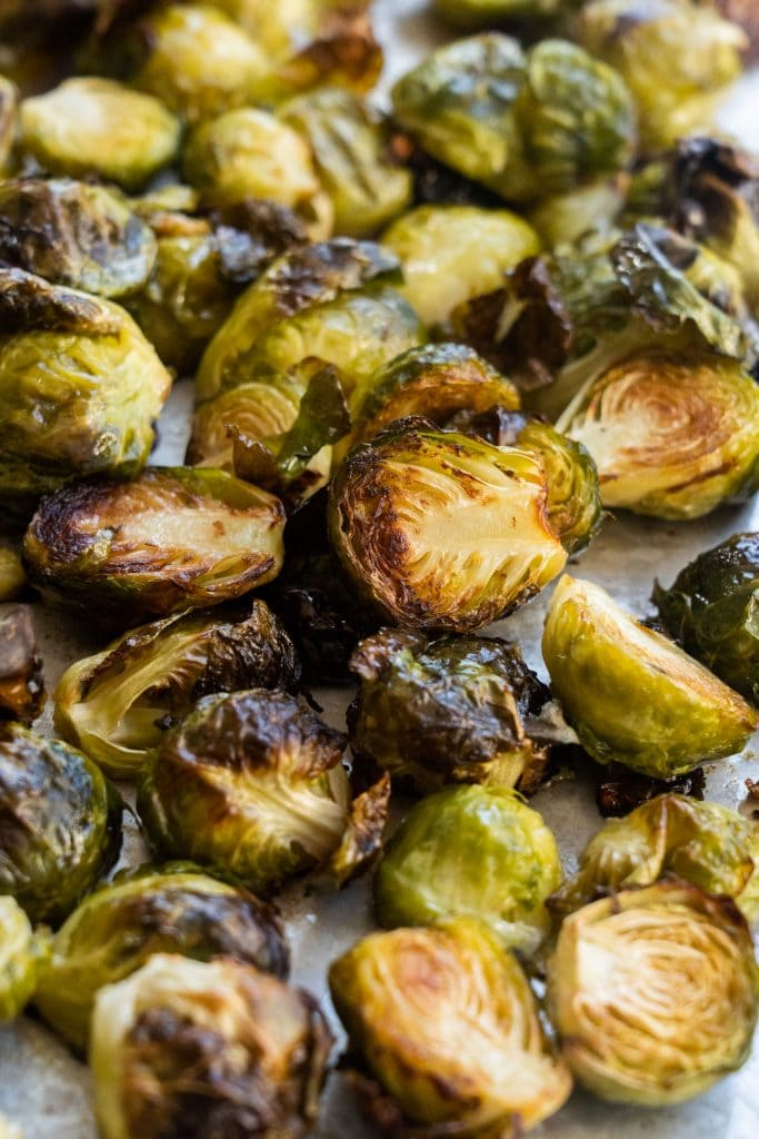 closeup of browned brussels sprouts on silver baking sheet