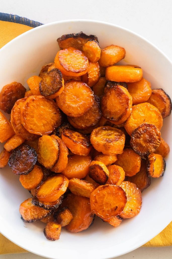 roasted carrots in white bowl on yellow napkin