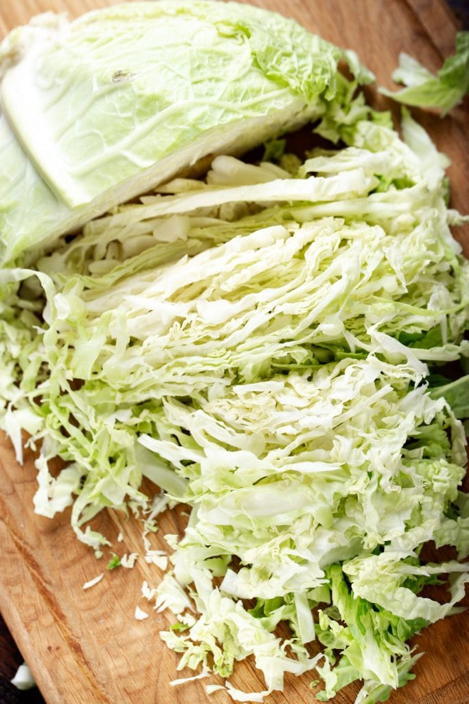 head of cabbage chopped up on cutting board