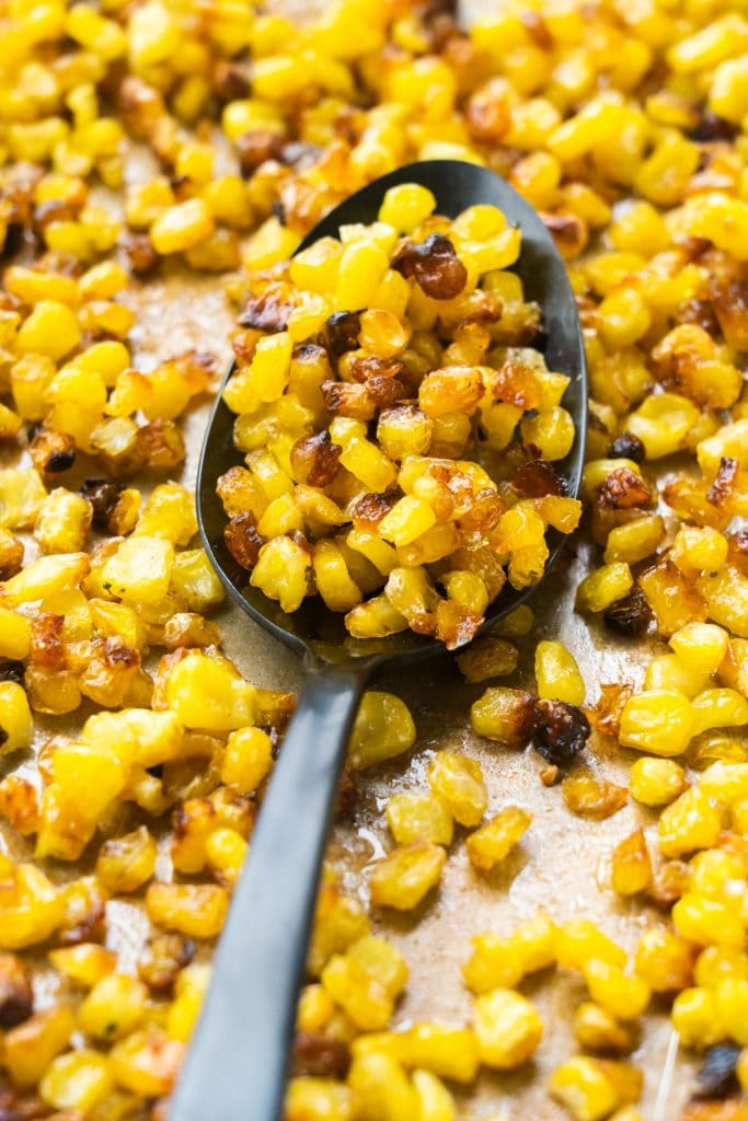 roasted corn on baking sheet with black spoon
