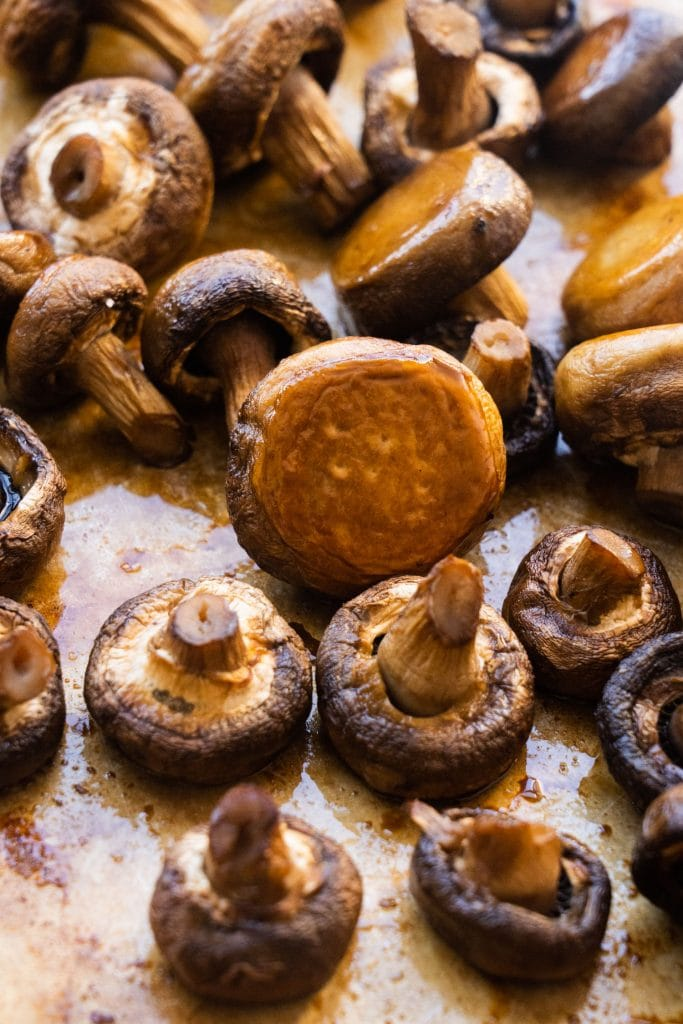 roasted mushrooms sitting on baking sheet after being cooked in the oven
