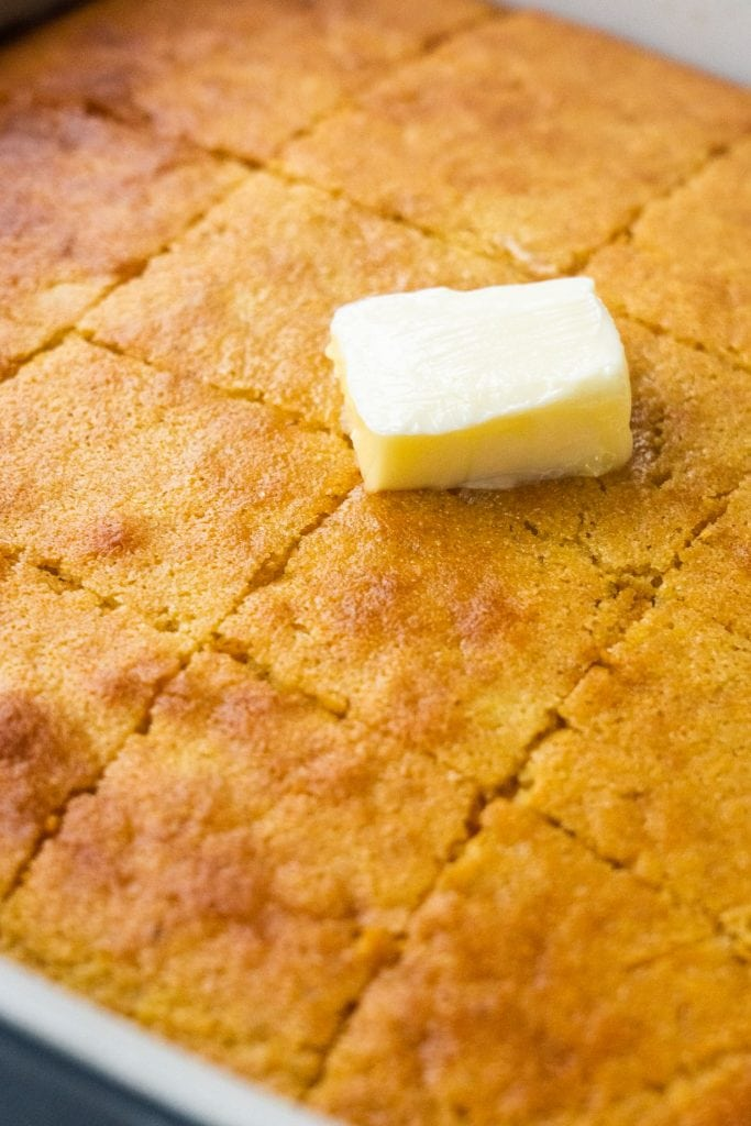 cornbread cut up with butter on it in baking dish