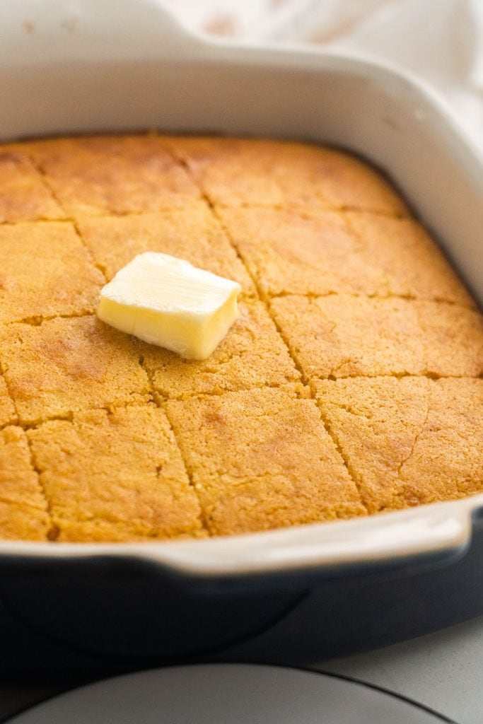 cornbread in white dish with butter on top