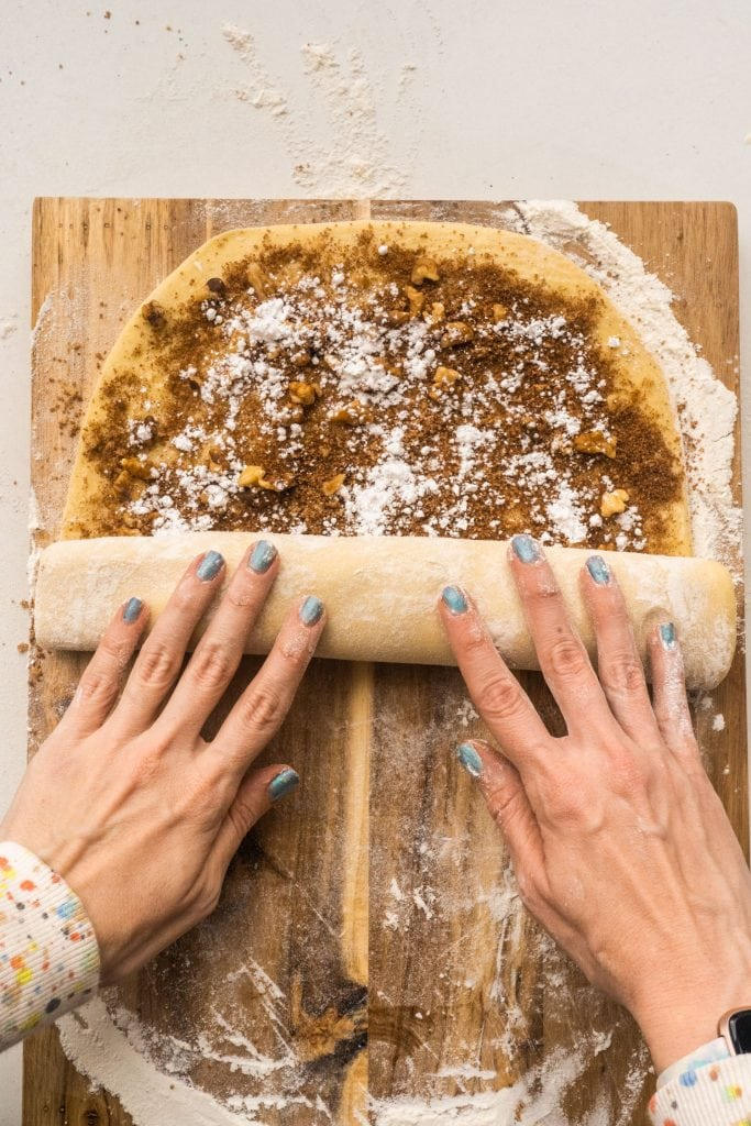 hands rolling dough up on cutting board