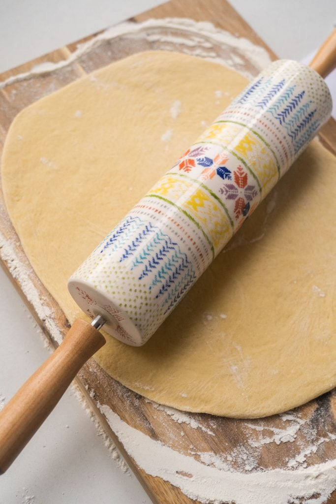 white and blue rolling pin with wooden handles rolling out dough on floured cutting board