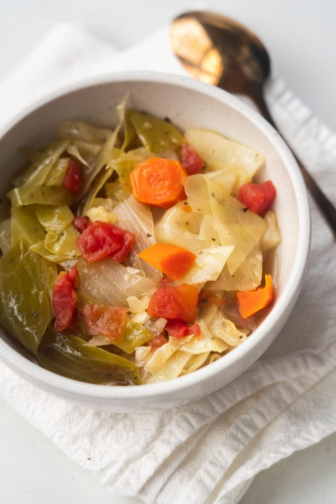 cabbage soup in white bowl on white towel