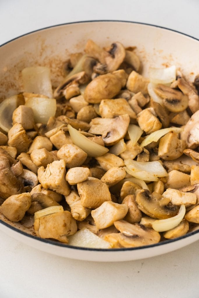 browned chicken with onion and mushrooms in skillet