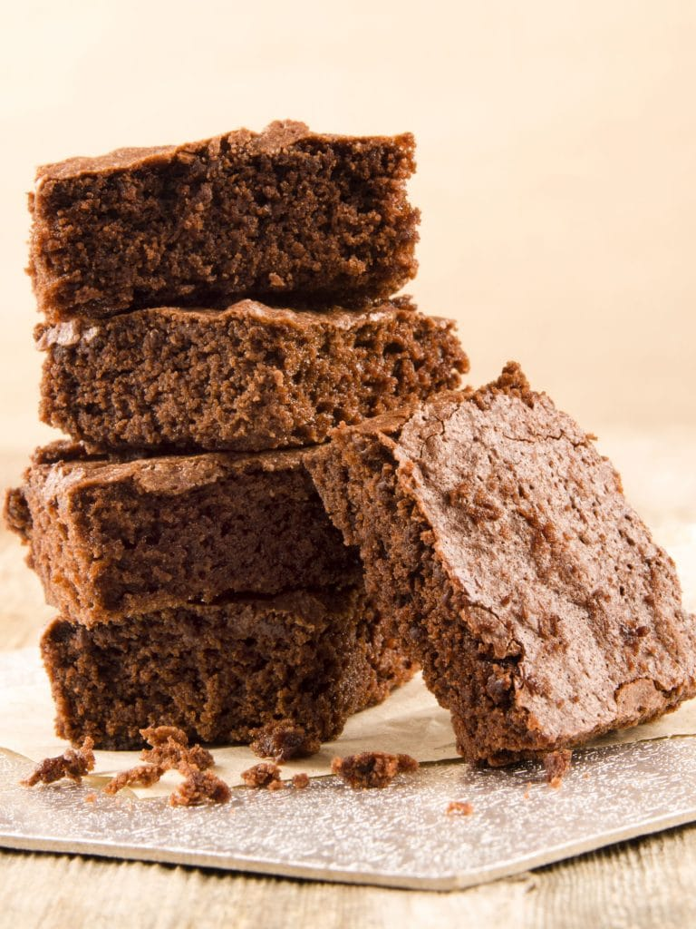 five coffee brownies on paper in front of brown background