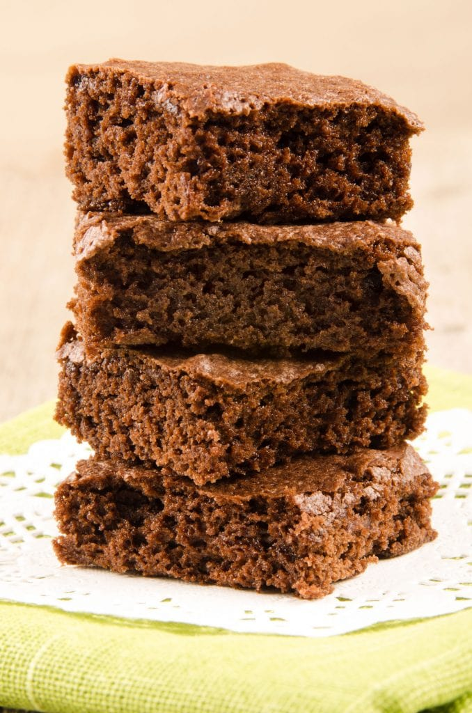 stack of coffee chocolate brownies on white towel whith brown background