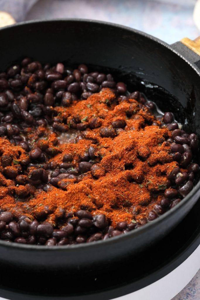 taco seasoning on top of black bean in skillet