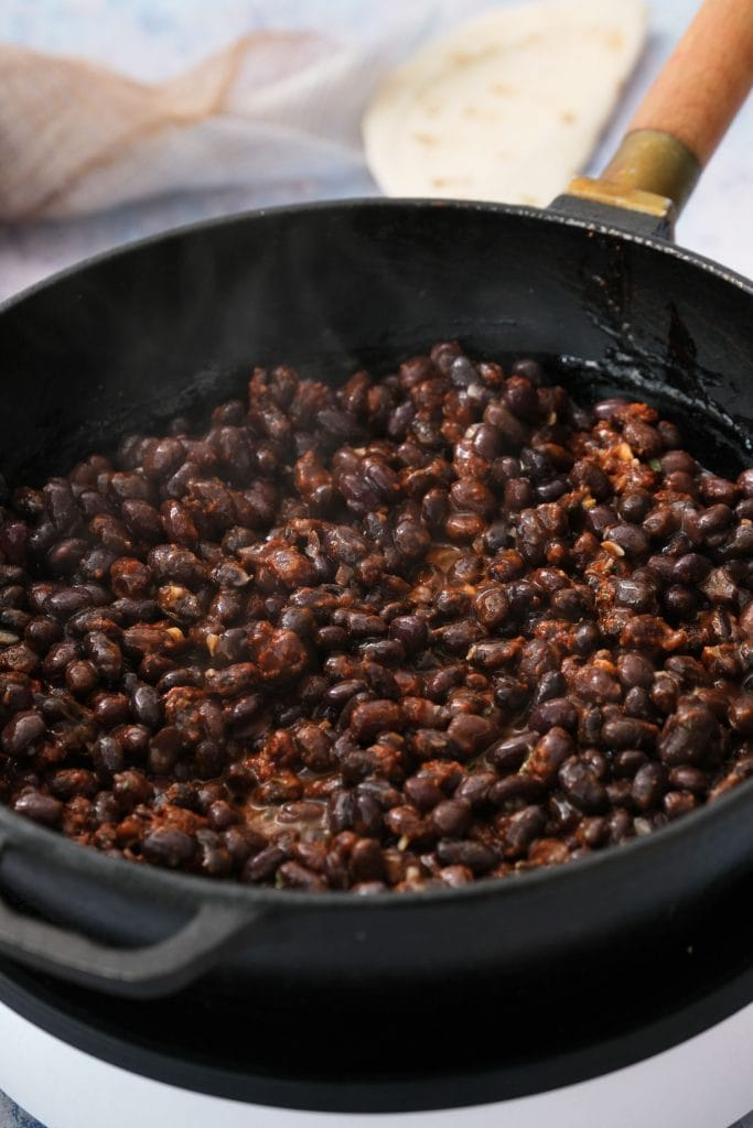 skillet with saucy black beans and taco seasoning