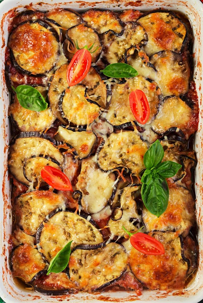 eggplant with shredded mozzarella cheese on top with fresh tomatoes and basil