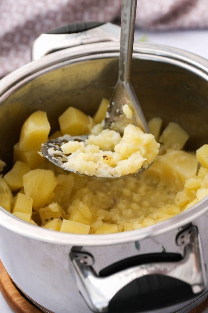 potato masher in pot to make colcannon.