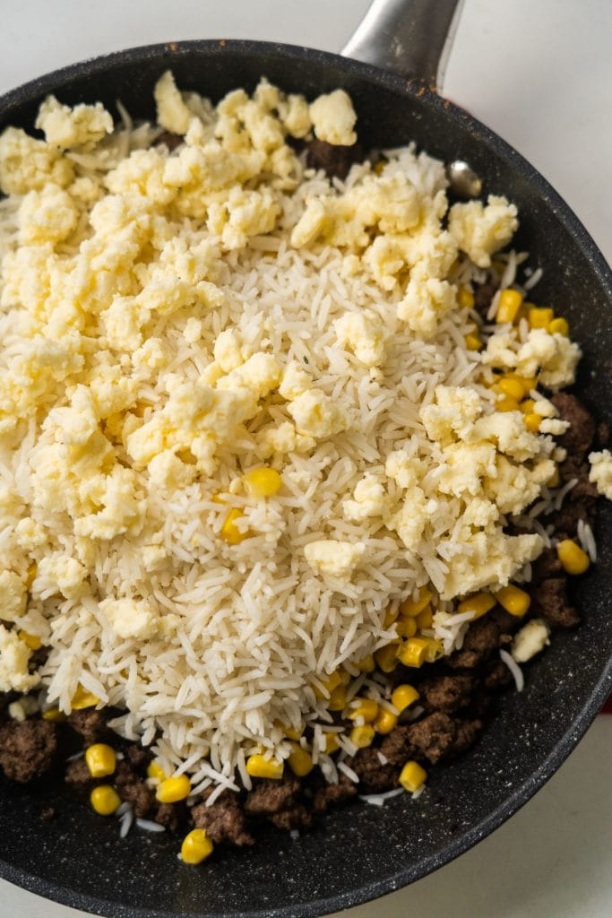 beef, corn, taco seasoning, rice and white cheddar cheese in skillet