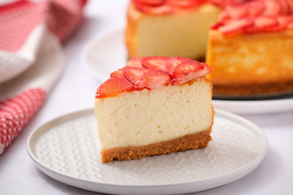 slice of cheesecake on white plate with strawberries on top