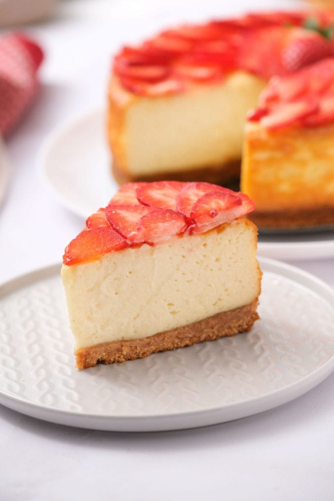slice of creamy new york cheesecake with strawberries on top