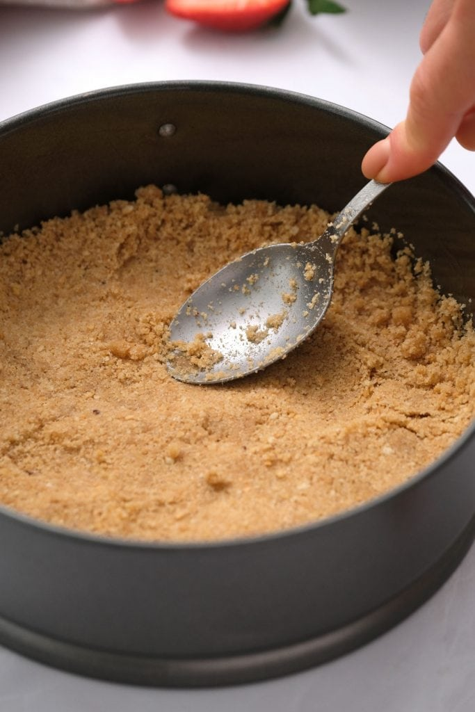 graham cracker crust being pressed into 9 inch pan