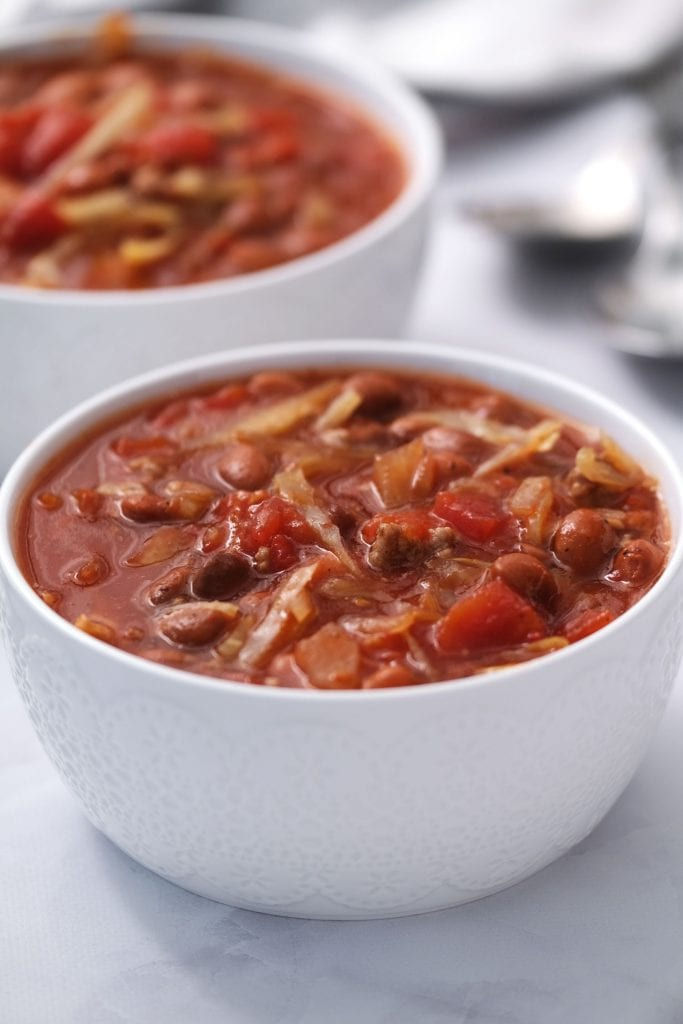 slow cooker cabbage soup in white bowls on white table.
