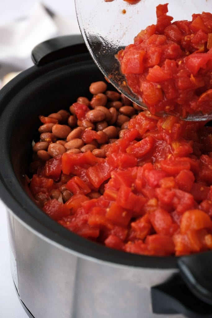 pinto beans and diced tomatoes being poured into crockpot.