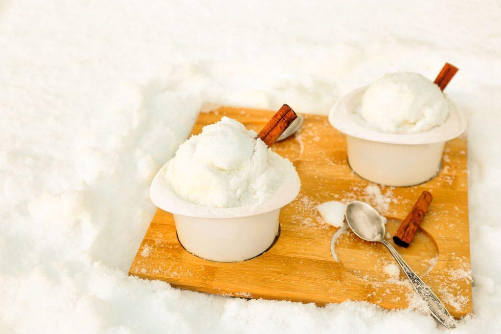 fresh snow ice cream on cutting board in white bowls with cinnamon sticks