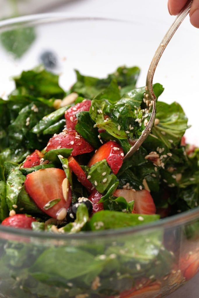 spoon mixing spinach and strawberries in glass bowl