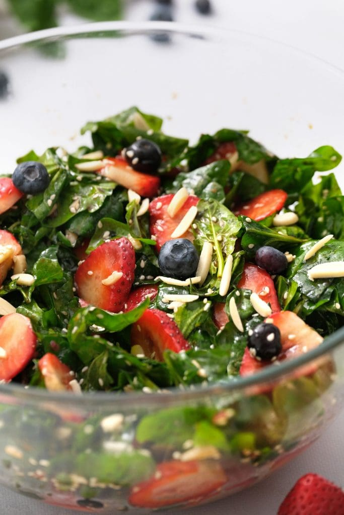 strawberry spinach salad with blueberries in glass bowl