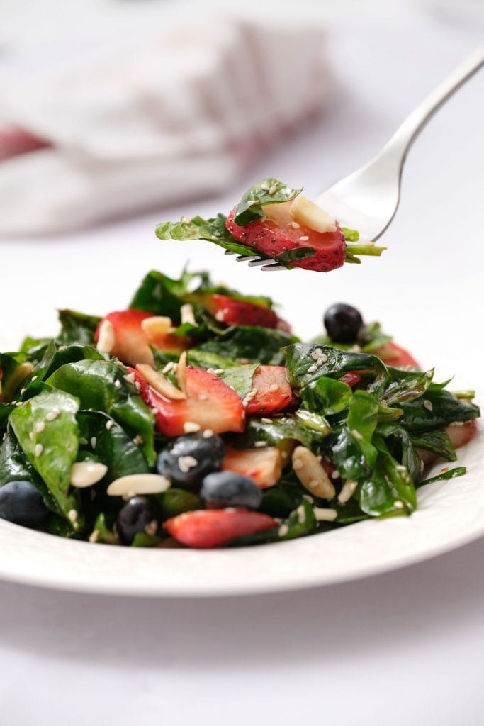 fork picking up strawberry spinach salad with strawberry and almonds on top