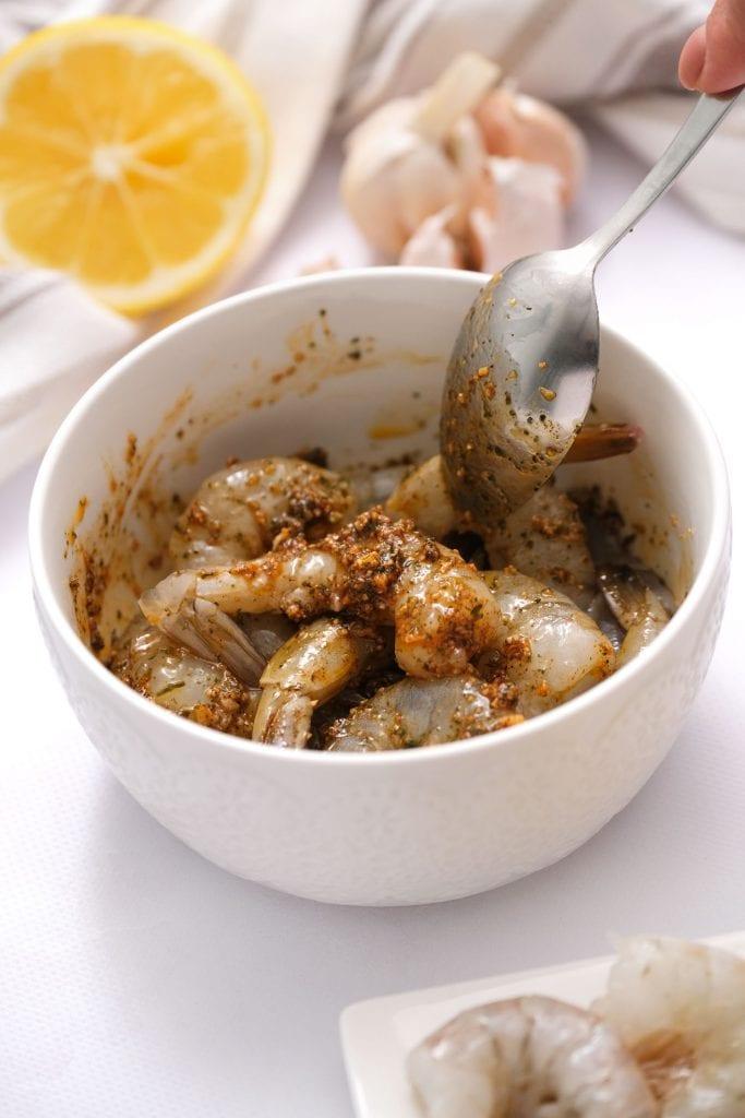 spoon stirring shrimp in white bowl
