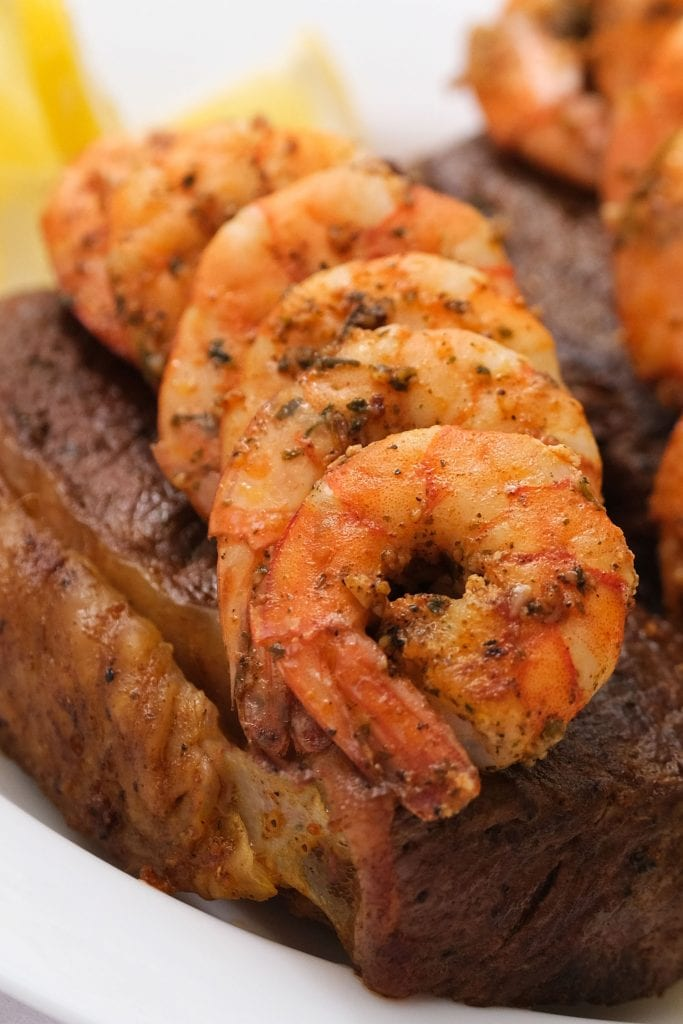 surf and turf recipe with marinated shrimp on top of new york strip steaks
