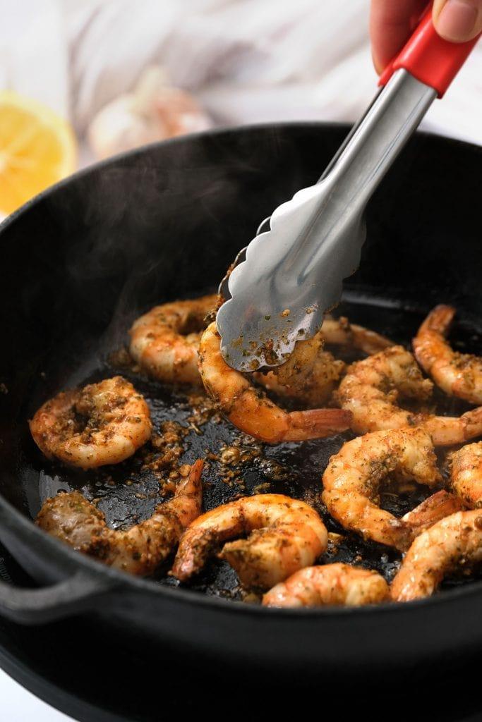 tongs flipping shrimp in skillet