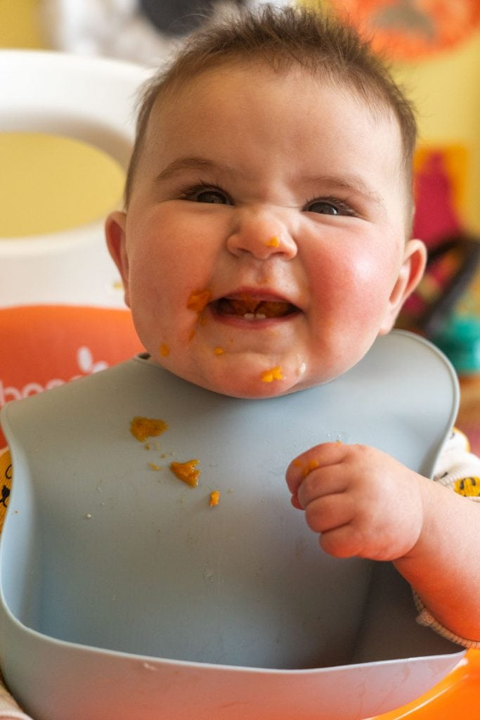 happy baby eating sweet potato fries.