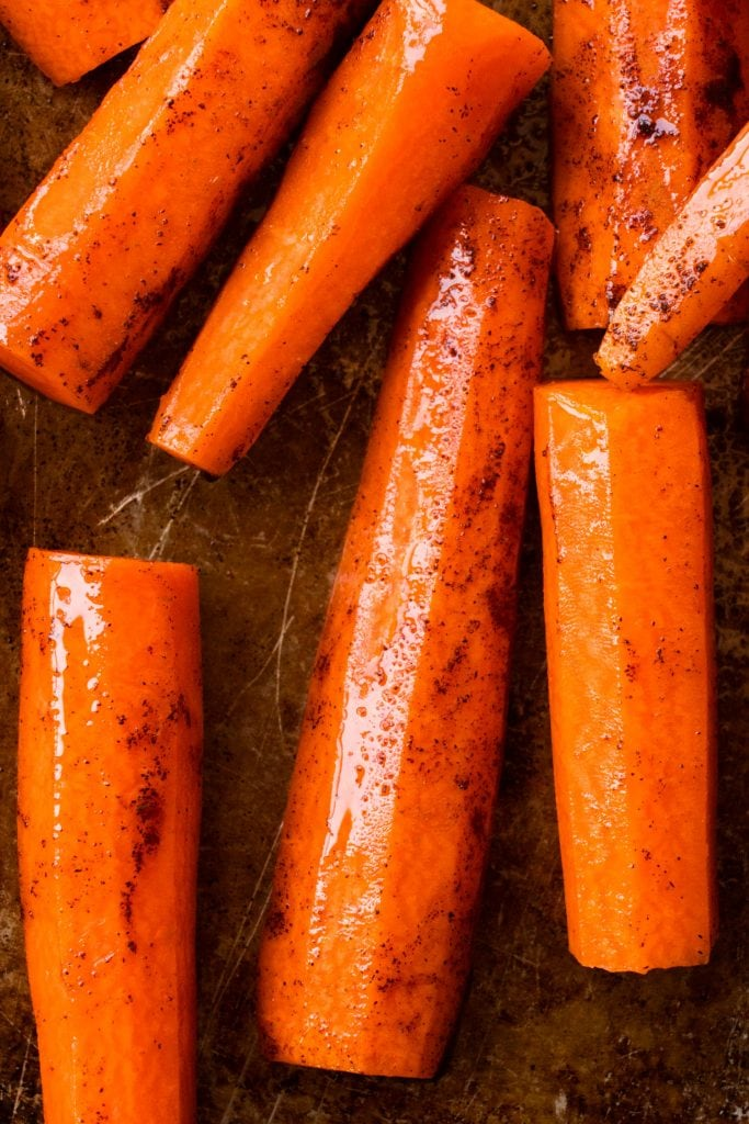 cinnamon and oil on carrots on baking sheet.
