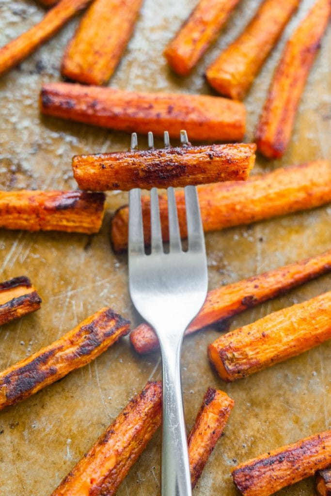 fork going into baked carrots on baking sheet.