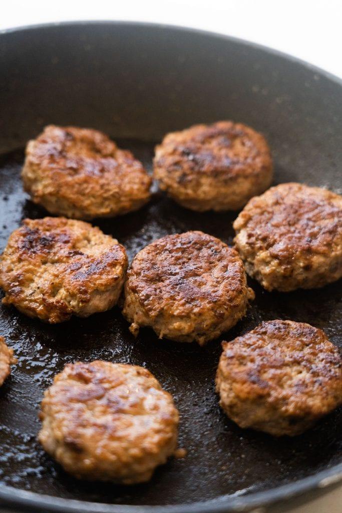 cooked sausage patties in frying pan